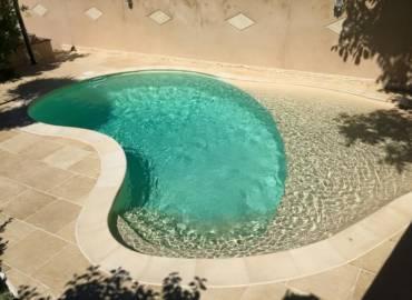 Piscina con playa de arena en membrana armada RENOLIT ALKORPLAN